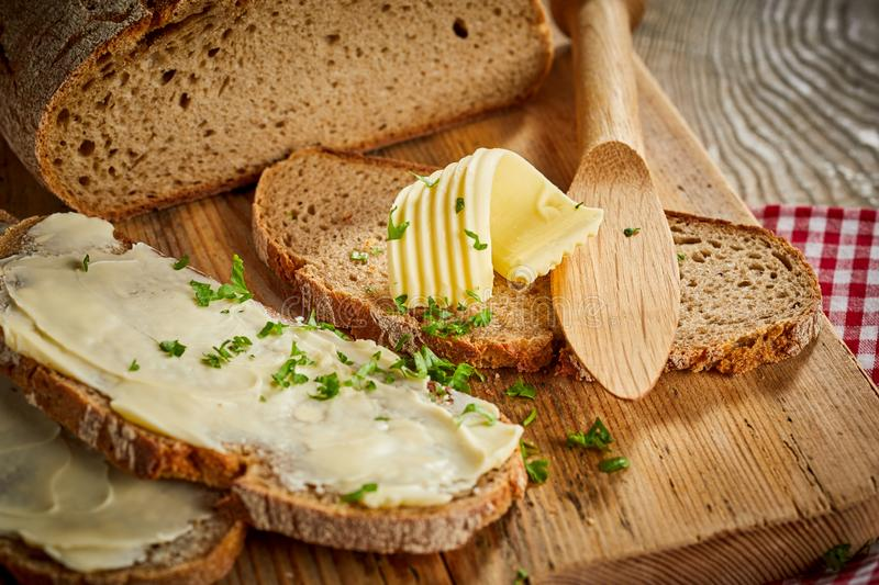 Buttered slices of fresh rye bread with parsley. Buttered slices of fresh rye bread topped with chopped parsley and a decorative twist or curl of butter on a royalty free stock image