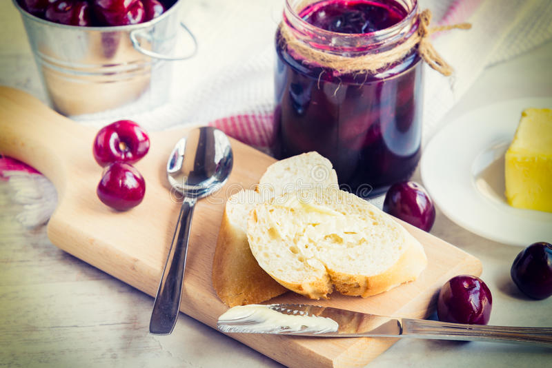 Buttered toasts and a jar with cherry homemade jam over white wood background royalty free stock images