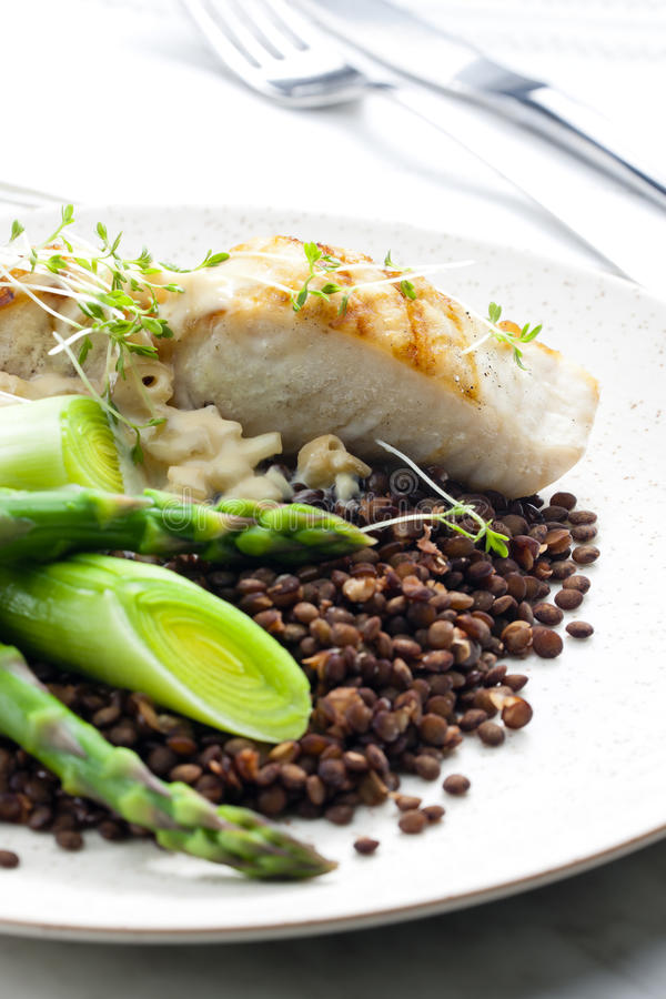 Butterfish with green lentils. Leek and green asparagus stock photography