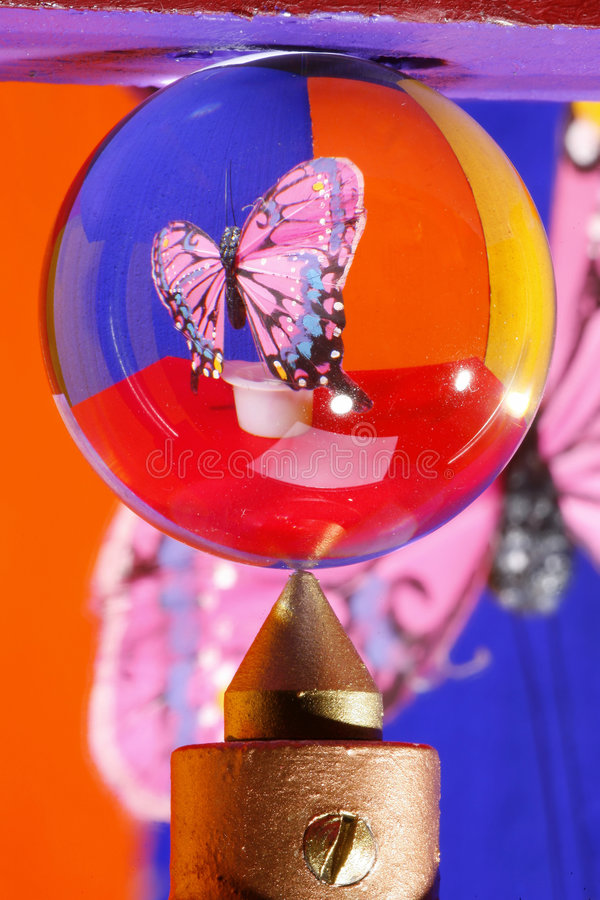 Butterfly in crystal ball. Ball of crystal glass, showing the projection of a silken butterly in front of colourful surroundings. The point is an industrial stock photos