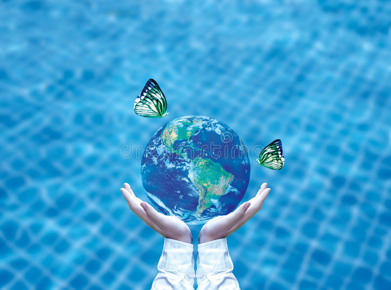 Butterfly drinking water from blue globe on hand. Saving water concept. Element of image furnished by NASA royalty free stock image