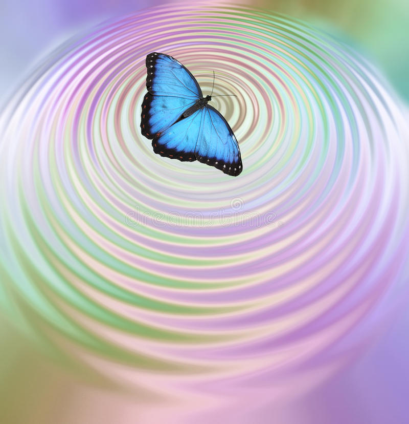 The Butterfly Effect. Big Blue Butterfly appearing to create ripples in pink green water surface with plenty of copy space below stock image