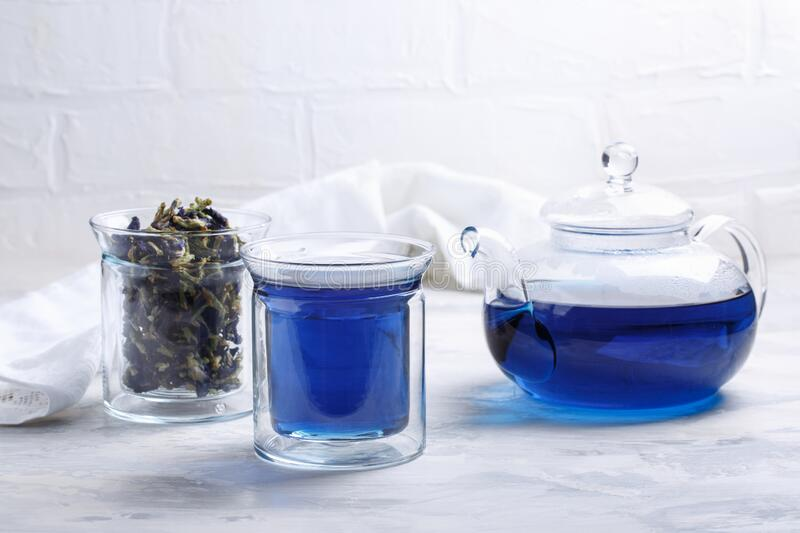 Butterfly pea flower tea is brewed in a glass teapot and served into a transparent cup. Blue herbal tea stock photography