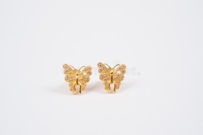 Butterfly shaped gold earrings. On the white background royalty free stock images