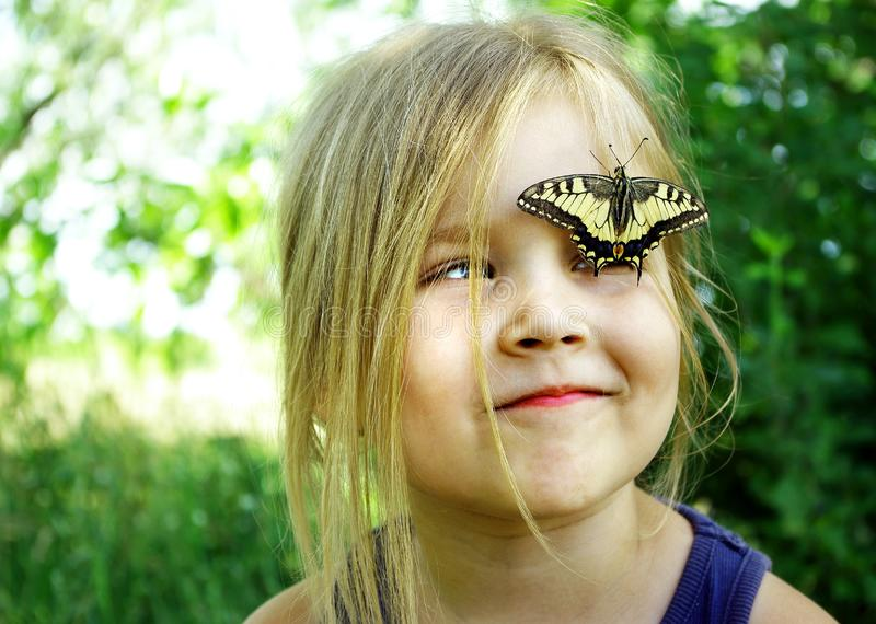 Butterfly sitting on a child. Child with a butterfly. Butterfly machaon on a little girl. Selective focus. Swallowtail butterfly,.  royalty free stock photography
