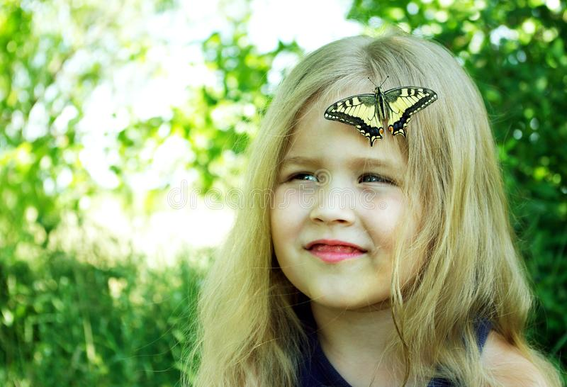 Butterfly sitting on a child. Child with a butterfly. Butterfly machaon on a little girl. Selective focus. Swallowtail butterfly,.  stock photos