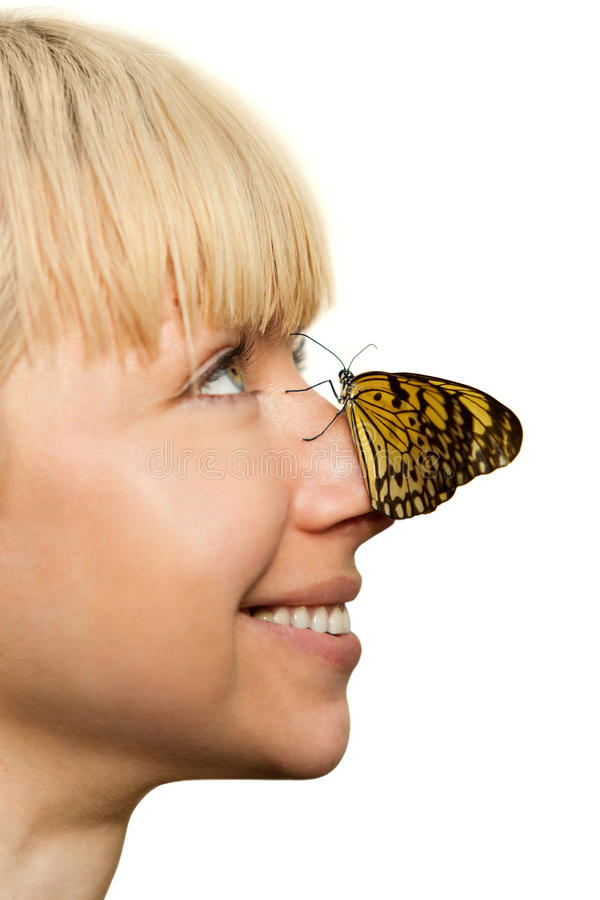 Butterfly sitting on the nose of smiling girl royalty free stock photo