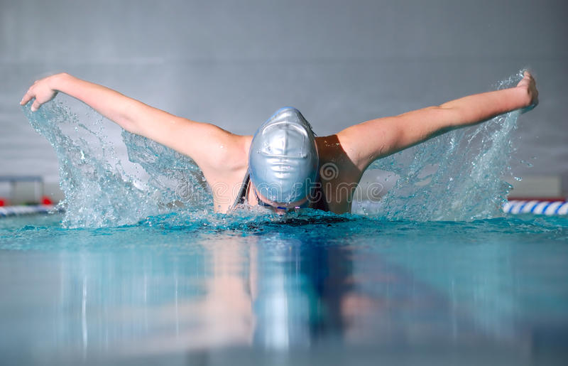 Butterfly stroke. Woman swims using the butterfly stroke in indoor pool stock photography