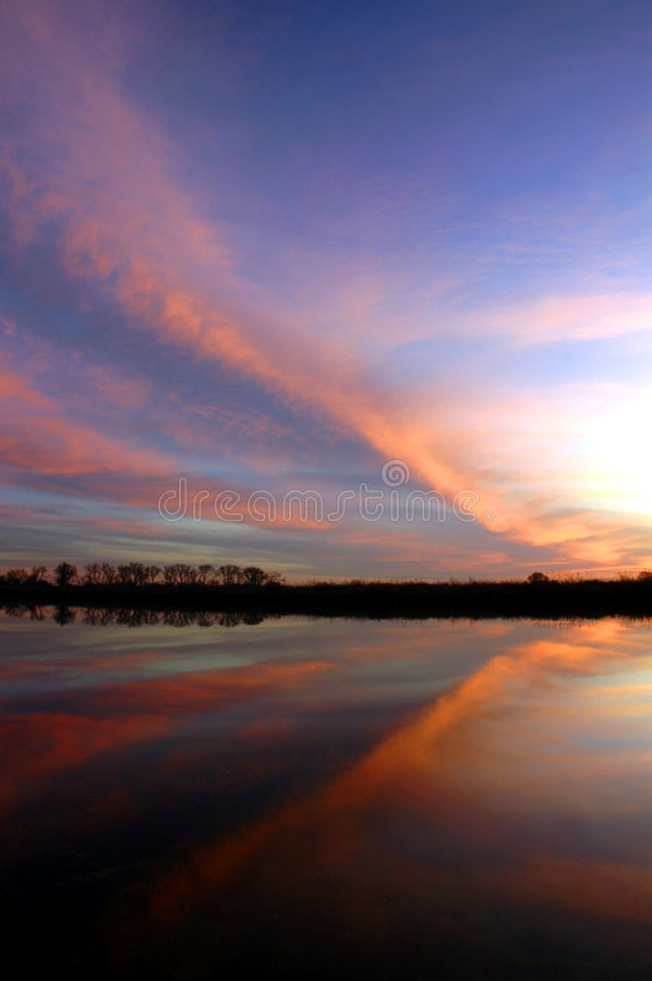 Butterfly Sunset. Striking Red Butterfly Cloud Formation Reflected at Sunset over Pond on Wildlife Preserve stock photo