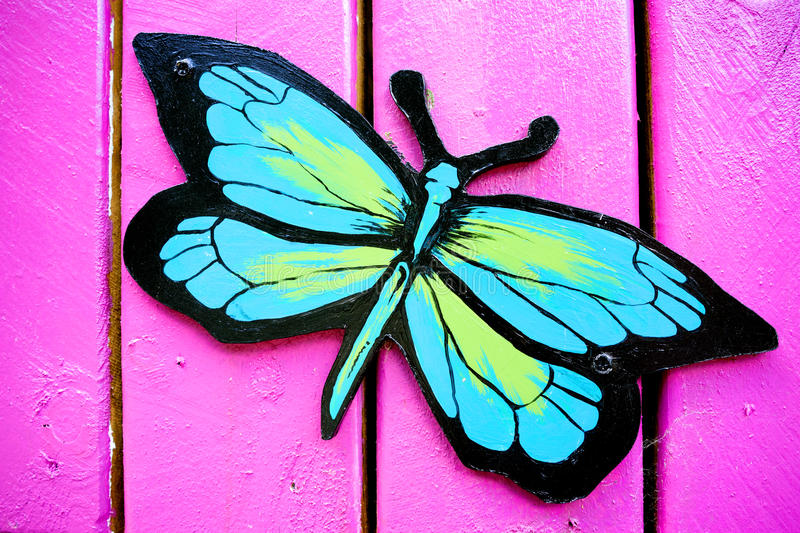 Butterfly Wall Decor. A wooden butterfly wall decoration mounted on a pink coloured wall royalty free stock photography