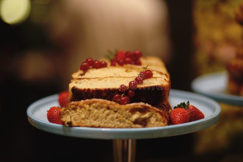 Butterkuchen verziert durch rote Johannisbeere und Erdbeere auf hellblauer Platte lizenzfreies stockbild