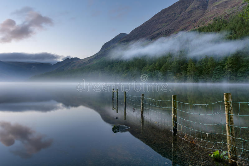 Buttermere湖在与薄雾和反射的黎明 库存图片
