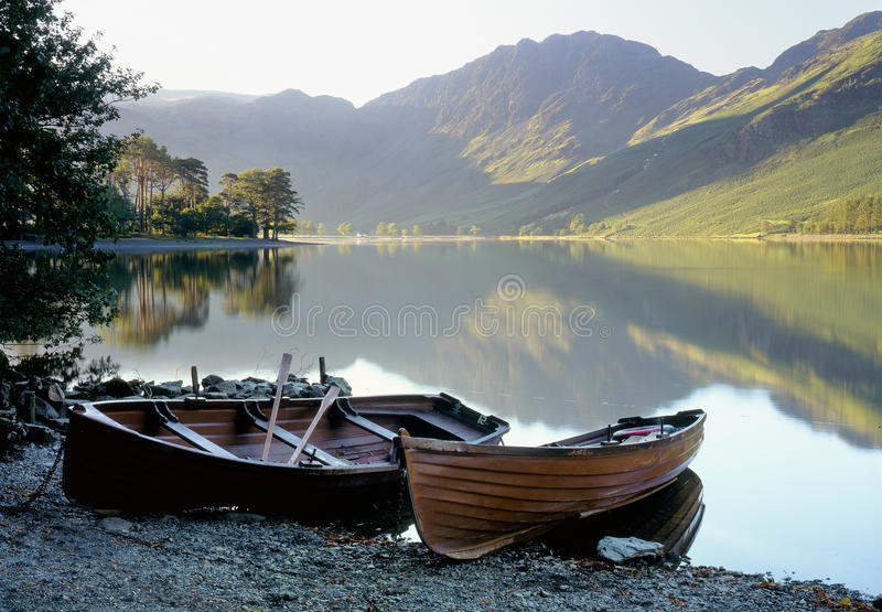 Buttermere rowboats, Lake district. First light on Buttermere, in the Lake district, Cumbria. The foreground rowboats are used for fishing, or for pleasure stock photography