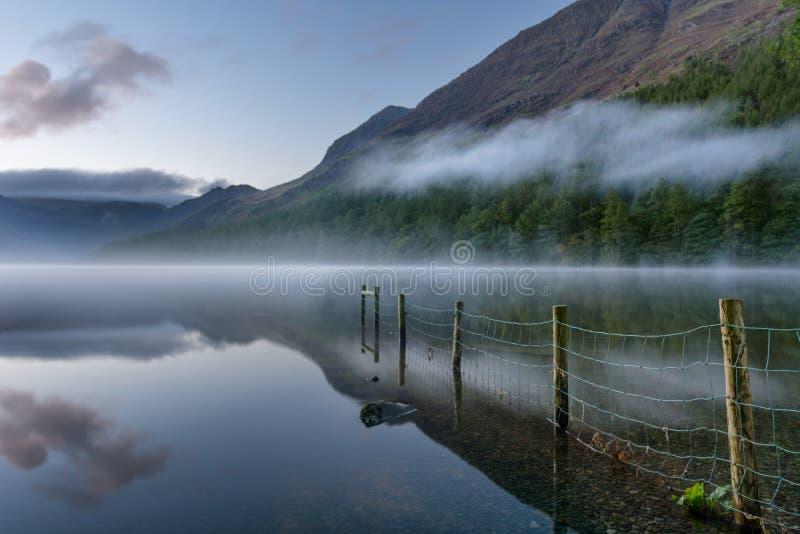 Buttermere sjö på Dawn With Mist And Reflections fotografering för bildbyråer