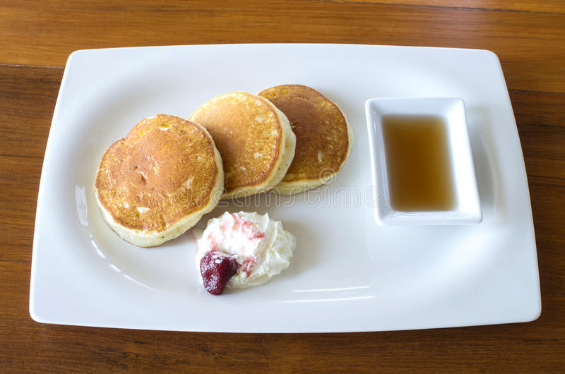 Buttermilk pancakes with maple syrup and weep cream in plate on. The wood table,thailand stock photos