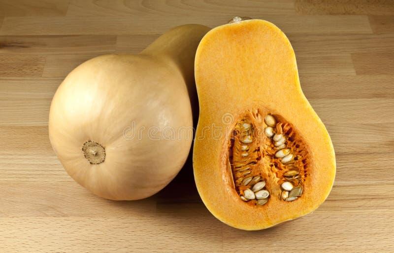Butternut Pumpkin. Bottle shaped butternut pumpkin, whole and cut stock image