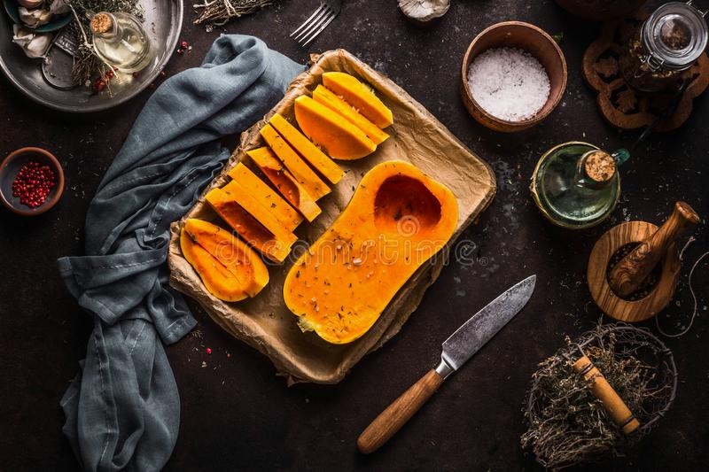 Butternut pumpkin halves on baking sheet. Cooking preparation on dark kitchen table background with herbs,spices, knife and. Utensils. Top view. Healthy royalty free stock images