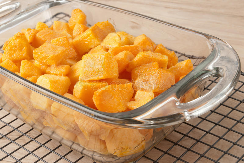 Butternut Squash. Fresh baked butternut squash drenched in olive oil prior to putting in the oven. Served in a see through glass pan and cooling off on a rack royalty free stock photos