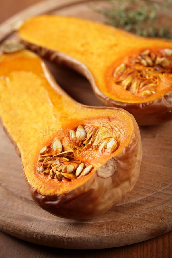 Butternut squash. Close up of baked butternut squash and herbs on wooden board stock photos
