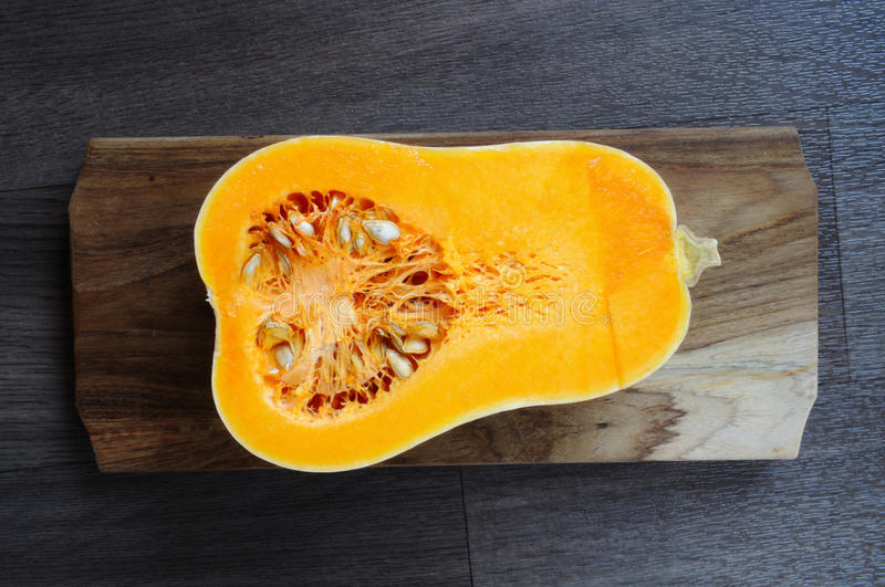 Butternut squash. Half of butternut squash lying on the wooden board royalty free stock image