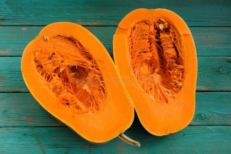 Butternut squash halved on wooden turquoise table royalty free stock images