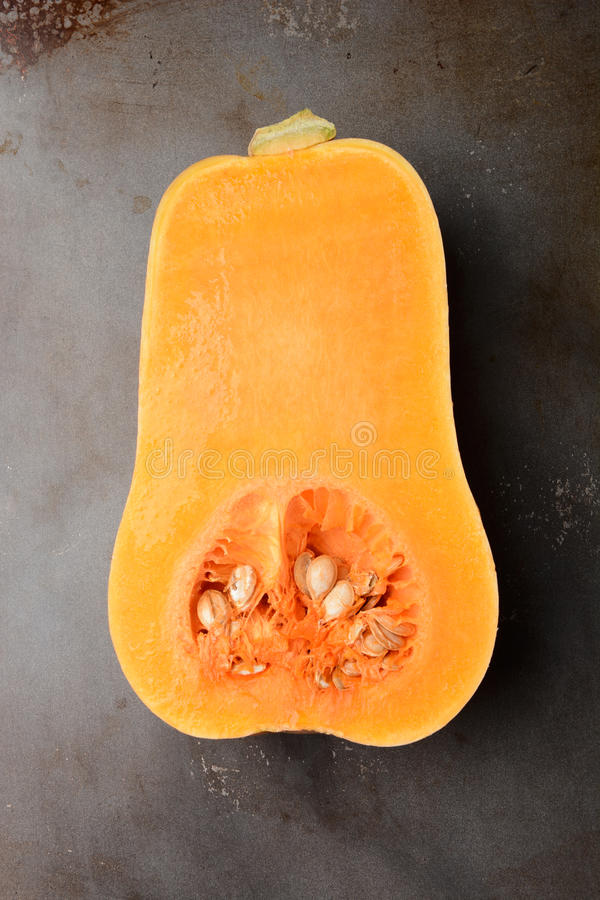 Butternut Squash. On a metal cooking sheet. The vegetable is cut in half showing the inside. Vertical format royalty free stock image