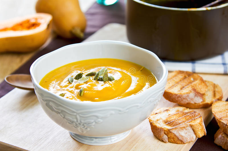 Butternut squash soup. By some toasts royalty free stock image