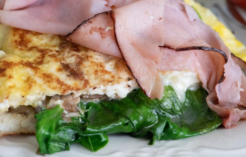 Buttery omelette with ham and spinach stock photos