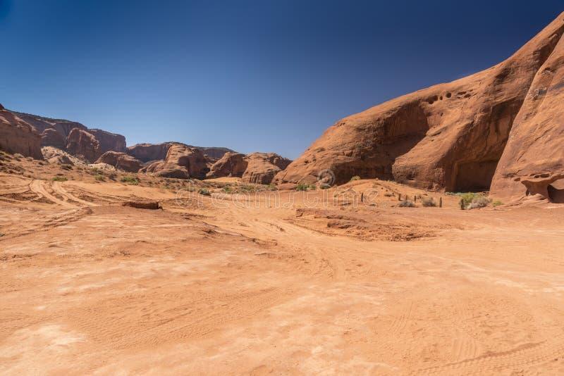 Buttes, växter och sand i monumentdalen Arizona royaltyfri foto