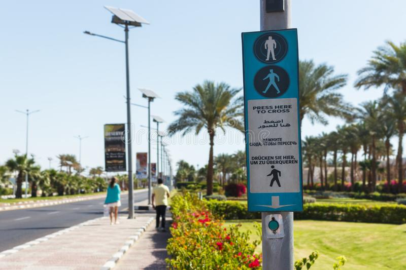 Button for calling the pedestrian crossing with the up arrow. click here to cross it written in four languages English, Arabic, Ru stock photo