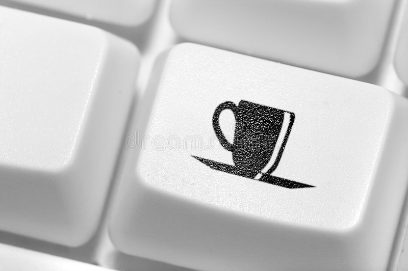button cup of coffee on the keyboard. A royalty free stock image