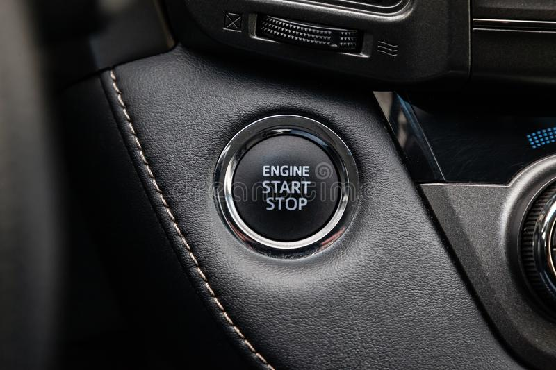 Button start and turn off the ignition of the car engine close-up on the dashboard, electric key, of modern design black and with. Elements chrome on the stock photos