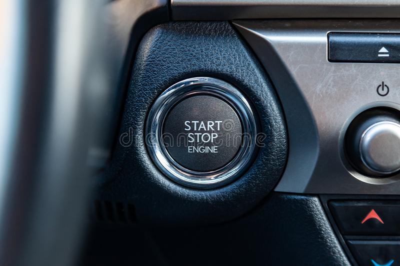 Button start and turn off the ignition of the car engine close-up on the dashboard, electric key, pressing drives the motor. Vehicle of modern design royalty free stock images