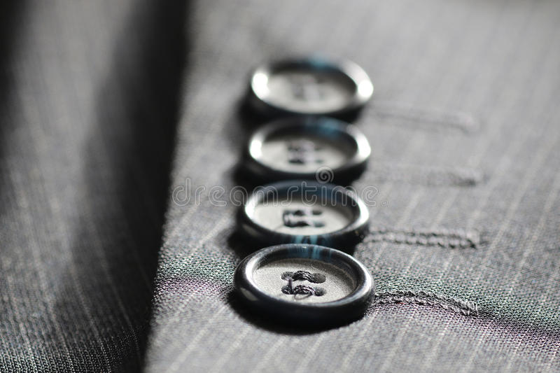 Button suit stripe. Four gray buttons sewn on the sleeve men's suit system stock image
