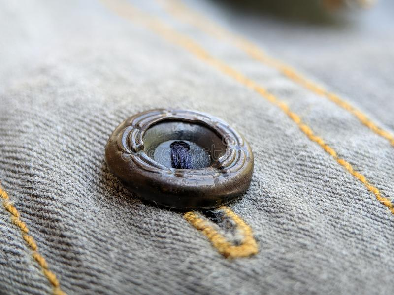 Button on a vintage dull brown shirt close up stock photo