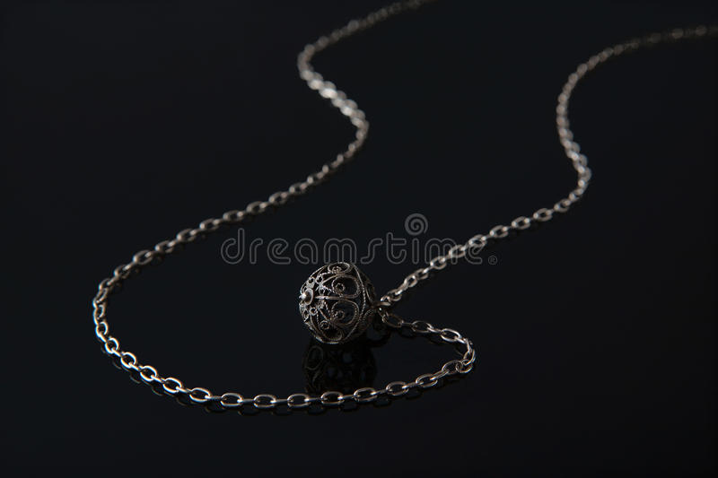 Buttons filigree. Antique silver spherical button, made in the technique of filigree, with silver chain on black glass royalty free stock image