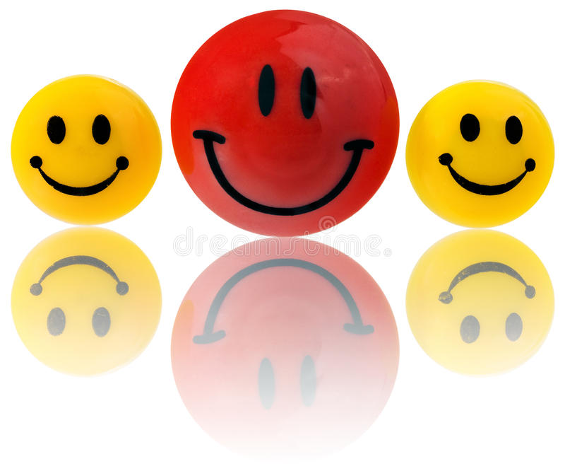Buttons, round smiling emoticons in yellow, red. Mounted on a magnet to the refrigerator. Smiling faces on a white background with slight reflection stock photos