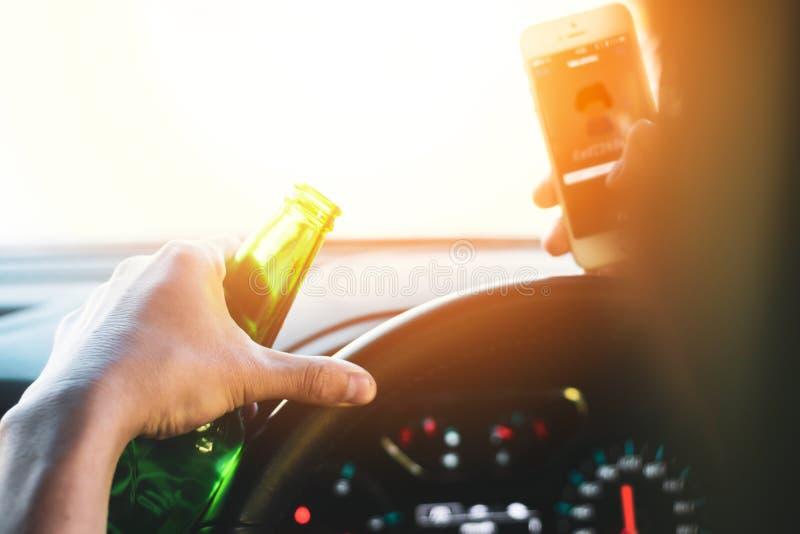 Buvant et conduisant, alcool d'homme et téléphone portable potables d'utilisation tout en conduisant la voiture, commande de conc photos stock