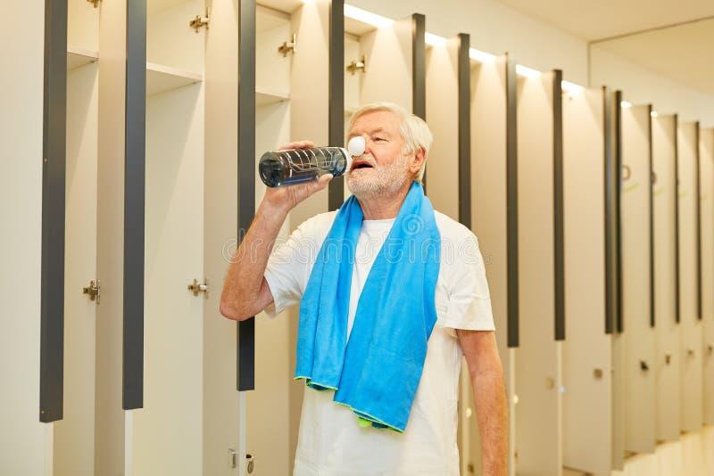 Buvettes seniors en soif à partir d'une bouteille d'eau photo libre de droits