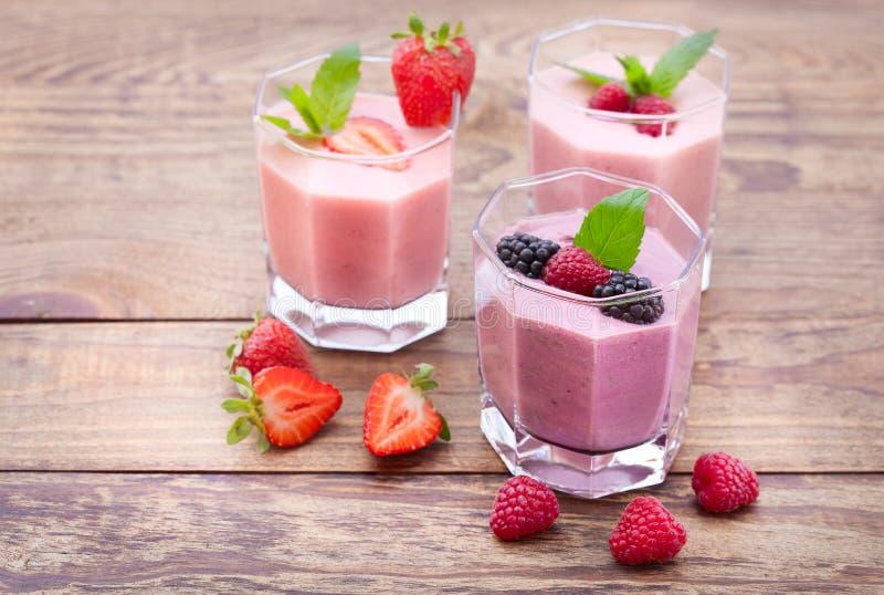 Buvez les smoothies fraise de quatre étés, mûre, le kiwi, framboise sur la table en bois image stock