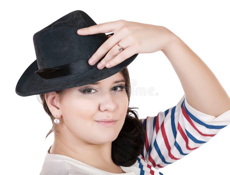 Buxomy ernstig meisje met een hoed op een wit stock foto's