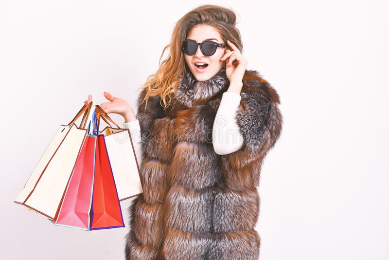 Buy with discount on black friday. Shopping or birthday gift. Girl wear sunglasses and furry coat shopping white. Background. Woman shopping luxury boutique royalty free stock image