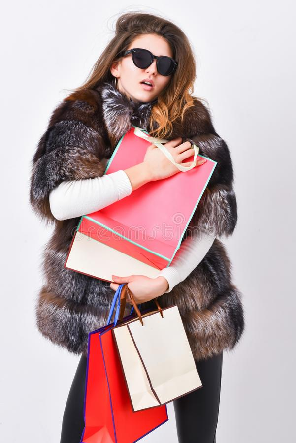 Buy with discount on black friday. Shopping with promo code. Girl wear sunglasses and fur coat shopping white background. Lady hold shopping bags. Discount and stock photo