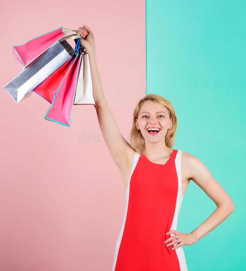 Buy everything you want. Girl satisfied with shopping. Tips to shop sales successfully. Woman red dress hold bunch. Shopping bags blue pink background. Girl stock photography