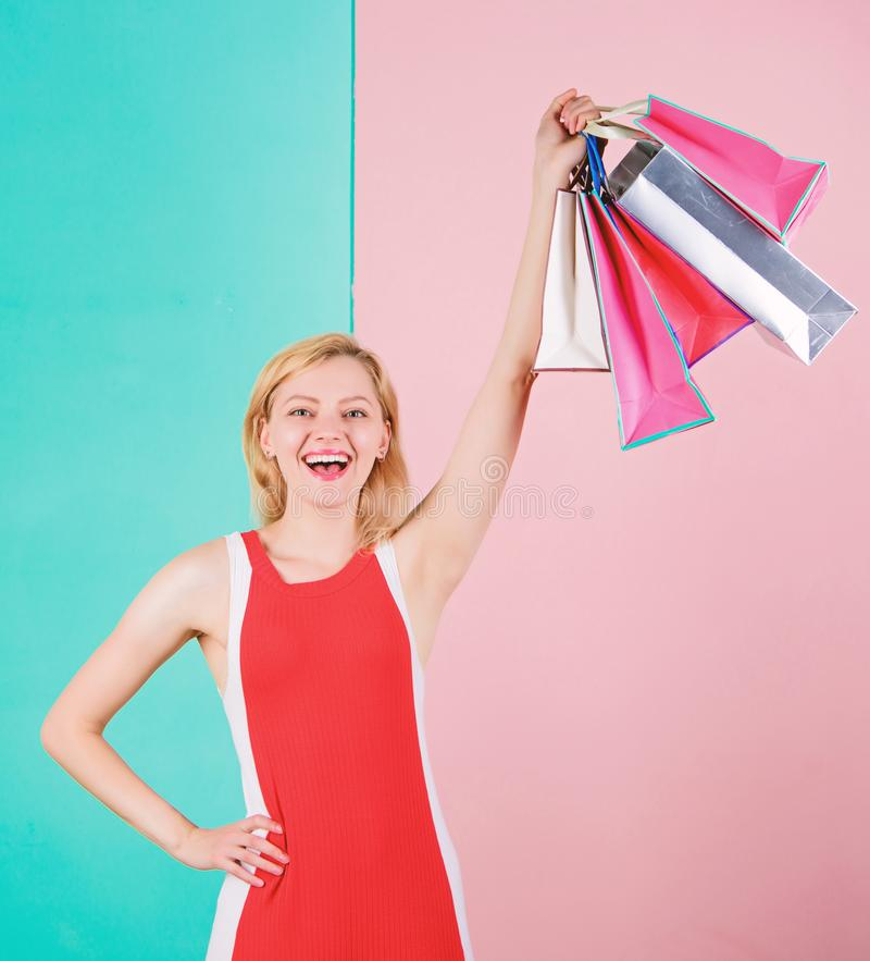 Buy everything you want. Girl satisfied with shopping. Tips to shop sales successfully. Woman red dress hold bunch. Shopping bags blue pink background. Girl royalty free stock images