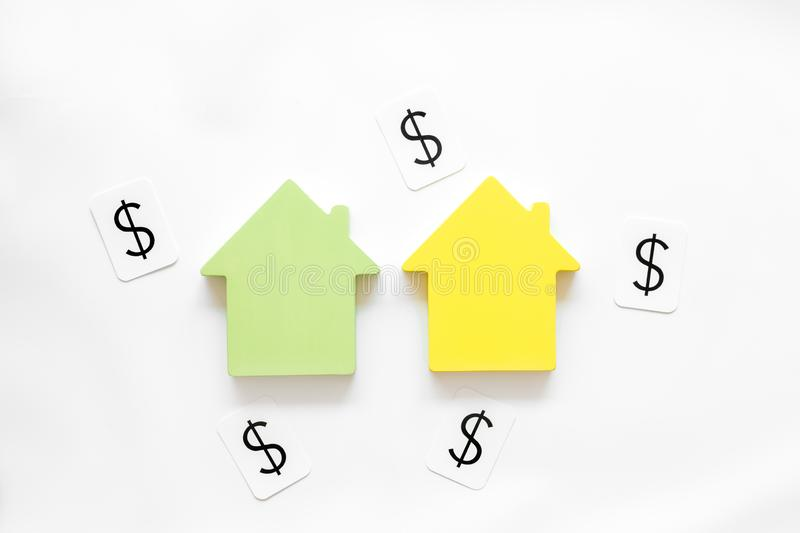 Buy house with house figure and dollar signs on office desk white background top view. Property insurance concept. Buy house with house figure and dollar signs royalty free stock image