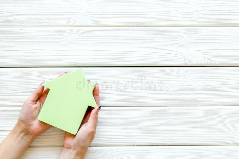 Buy house with house figure in hands on office desk white wooden background top view mock-up. Property insurance concept. Buy house with house figure in hands on stock photo