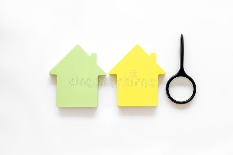 Buy house with house figure and magnifier on office desk white background top view. Property insurance concept. Buy house with house figure and magnifier on stock photo
