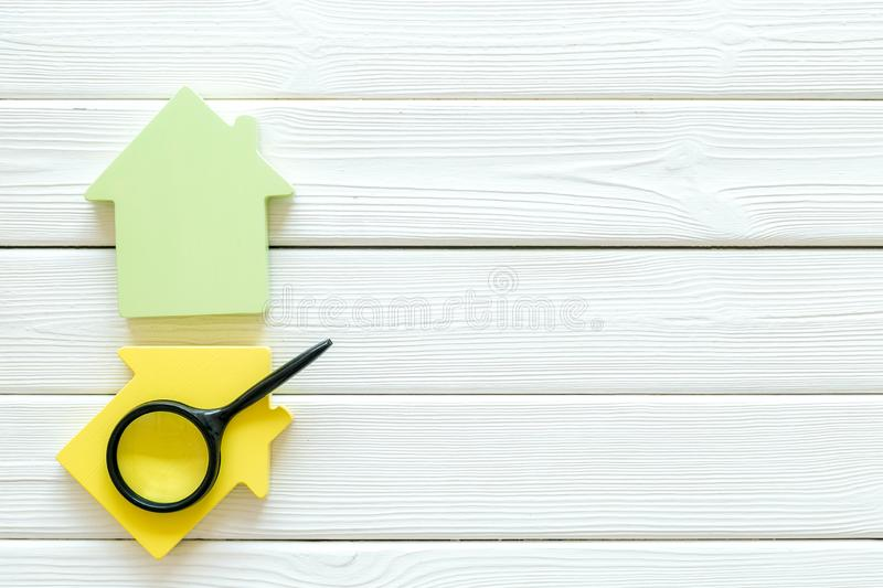 Buy house with house figure and magnifier on office desk white wooden background top view mock-up. Property insurance concept. Buy house with house figure and royalty free stock images