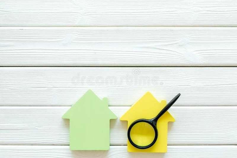 Buy house with house figure and magnifier on office desk white wooden background top view mock-up. Property insurance concept. Buy house with house figure and royalty free stock photo